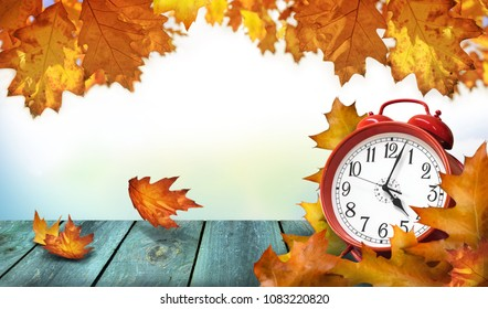 Clock and autumn leaves on the wooden table - daylight saving time concept