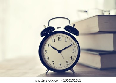 Clock and books on table