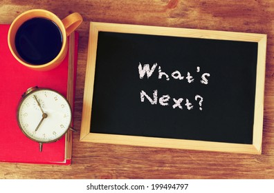clock, coffee, and blackboad with the phrase whats next? written on it.