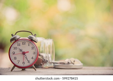 Clock with Coins and glass containers in Natural background.Business finance. Save money for investment,education concept