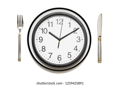 Clock dinner plate with a fork and knife on white background. Clock on plate and knife and fork on white background, top view. Lunch time concept