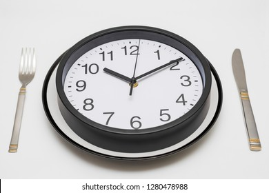 Clock dinner plate with a fork and knife on white background. Clock on plate and knife and fork on white background. Lunch time concept