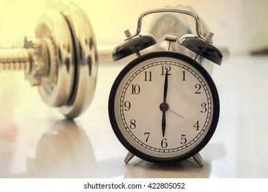 Clock and dumbbell background. Fit and firm concept.