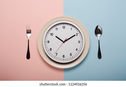 Clock and empty plate on pastel background