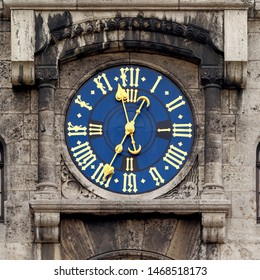 Clock at Fabercastell Schloss (Palace) in Stein near Nuremberg, Germany. Golden fingers and numerals on blue clock face. Time on clock: 11h35