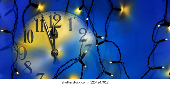 Clock face and Christmas electric light before midnight