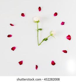 Clock face made of rose petals. Flower clock flat lay. Time concept