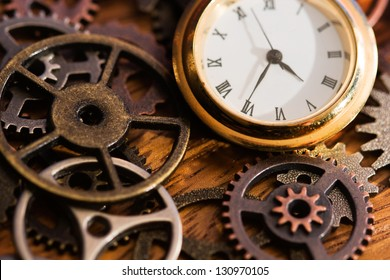 A clock face and old gears on a wooden surface.
