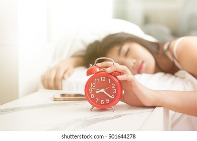 A clock and the feet of a sleeping woman. Early morning.sleeping young female disturbed by alarm clock early morning on bed