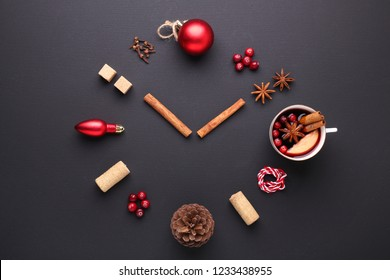 A clock in the form of spice for mulled wine. Cinnamon, anise stars, cranberries, brown sugar. Concept, creative work. Time to cook mulled wine. Top view. Black background