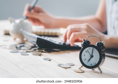 Clock with Hand holding pen write note with Coin money piggy bank using calculator on wooden table growth saving money with take time, Concept financial business investment, Copy space for your text.