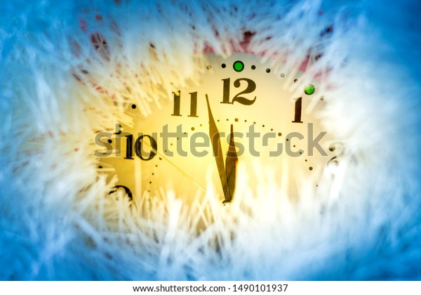 The clock hands indicate the approach of the new year. Clock with festive decorations on New Year's night in yellow and blue