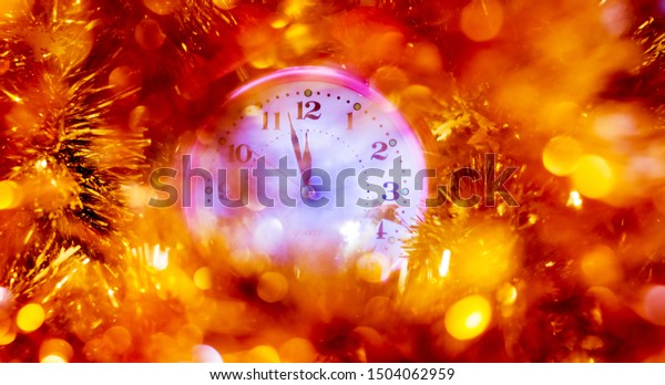The clock hands indicate the approach of the new year. Clock with festive decorations on New Year's night