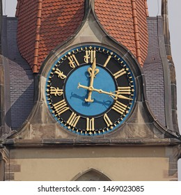 Clock at Heilig-Geist-Kirche (Church of the Holy Ghost) in Basel, Switzerland. Golden fingers and numerals on blue/black clock face. Time on clock: 00h17