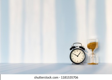 Clock with hourglass on white background