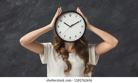 Clock instead of head. Girl hiding over alarm, stress and lack of time concept