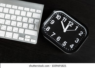 Clock and keyboard on a dark table. Business and education