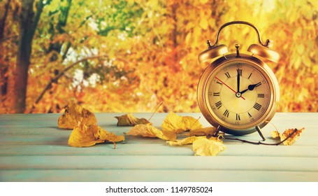 Clock and leaves on wooden table.
