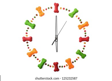 A clock made of dog biscuits and dog food isolated on a white background showing 6 o'clock.