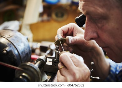A clock maker and repairer using an eye loupe to work on a cog wheel, clock parts
