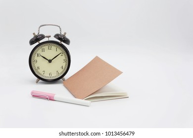 Clock, notebook, ballpoint pen on white background with clipping path.