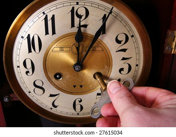 clock, old vintage time piece in wood and brass showing just past twelve or midnight wind-up