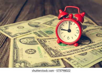 Clock on background of dollars. Concept of money is time. Toned image.