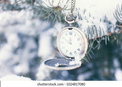 the clock on the chain hangs on the branches of the Christmas tree in the snow. The time is indicated at 11:50