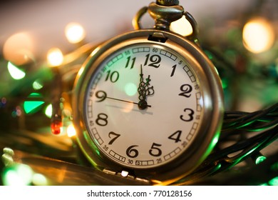 clock on a chain in the lights of a garland. The time on the clock 11:55 PM