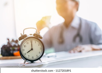 Clock on doctor clinic table for times to healthcare checkup time appointment concept.