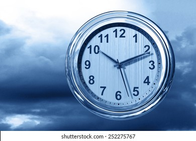 Clock on dramatic blue sky background