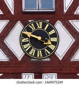 Clock on half timbered facade of hospital church in Hollfeld, Germany. Golden fingers and numerals on black clock face. Time on clock: 03h49