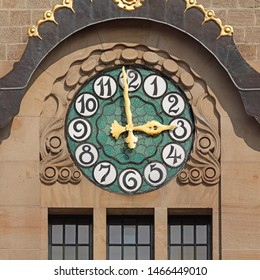 Clock on Kaufhaus (department store) in Basel, Switzerland in jugendstil style. Golden fingers and black numbers on decorative green clock face. Time on clock: 02h59