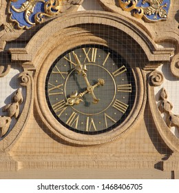 Clock on Palais Stutterheim, Erlangen, Germany. Golden fingers and numbers on grey clock face. Time on clock: 07h56