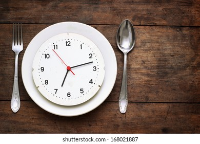 Clock on the plate on wooden background