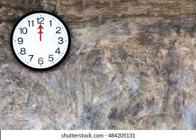 Clock on polished plaster walls at 12 noon