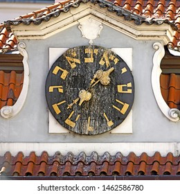 Clock on Židov ská radnice (Jewish town hall) with hebrew numbers in Prague, Czech Republic. Golden fingers and numbers on black clock face.