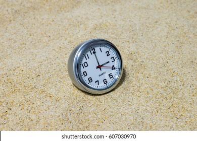 Clock on sand background