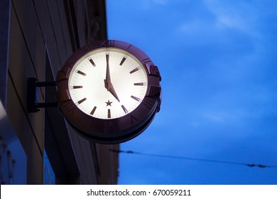 Clock on the wall in street in city with blue sky on background