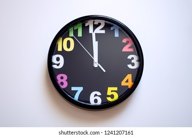 Clock on a white background. A few seconds to midnight. Multi-colored numbers on the clock.