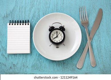 Clock on white plate with fork, knife and notepad, intermittent fasting and weight loss plan concept