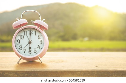 Clock on wood in the morning, blurred nature background.