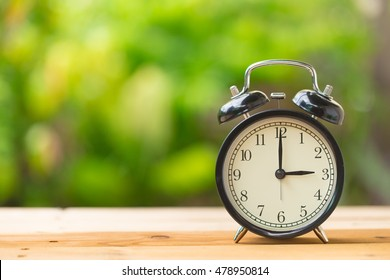 clock on wood table in the green garden time at 3 o'clock