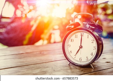 clock on wood table with sunlight effect in the morning times at 7 o'clock.