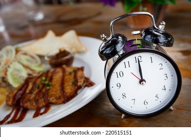 Clock on Wooden Table with steak on background, Lunch Time Concept