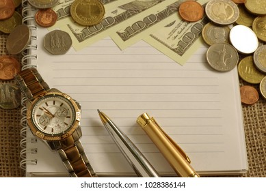 clock pen notepad and money