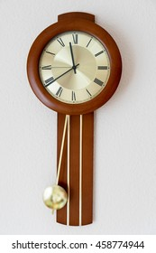 Clock with pendulum hanging on a wall