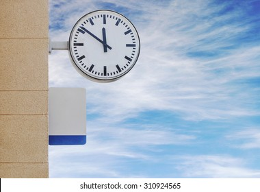 Clock and plate for information at train station, cloudy sky background