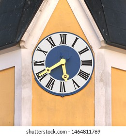 Clock of Roman Catholic Parish Church Saint Margret in Geiselhöring - Oberharthausen, Bavaria, Germany. Golden fingers and black numbers ond blue/white clock face. Time on clock 05:40
