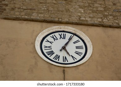 a clock with roman numbers on a wall of a building in Pititgliano